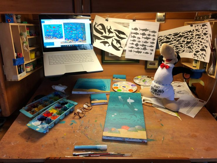 This is a photo of a painting desk, with canvases and paints. On the desk is a stuffed toy Opus, a penguin character from the comic strip, Bloom County